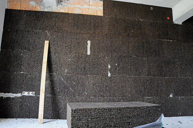 Cork boards behing installed on a brick wall seprating 2 apartments in Amadeo 2